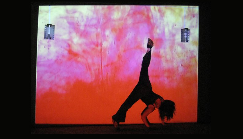 screenshot of video with dancer in front the fluid projection